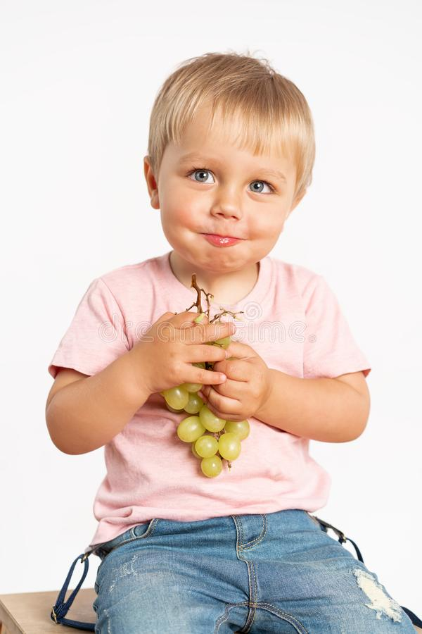 Baby boy eating grapes and smiling in the studio isolated on white background. Concept healthy food royalty free stock images