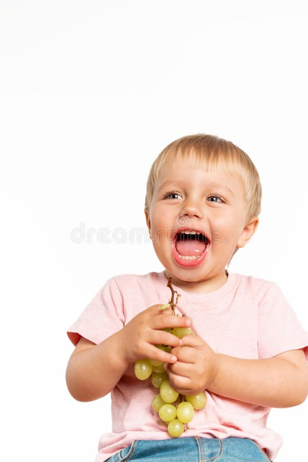 Baby boy eating grapes in the studio isolated on white background. Concept healthy fresh food royalty free stock photos