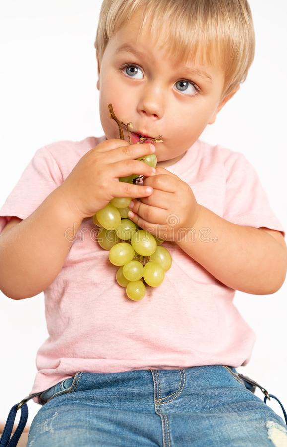 Baby boy eating grapes in the studio isolated on white background. Concept healthy fresh food stock photos