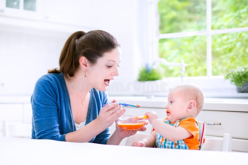 Baby boy eating his first solid food witn his mother stock photo