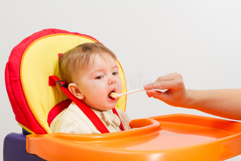 Baby boy eating with spoon at home stock photos