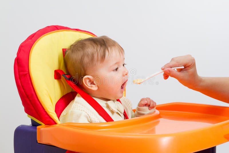 Baby boy eating with spoon at home royalty free stock photo