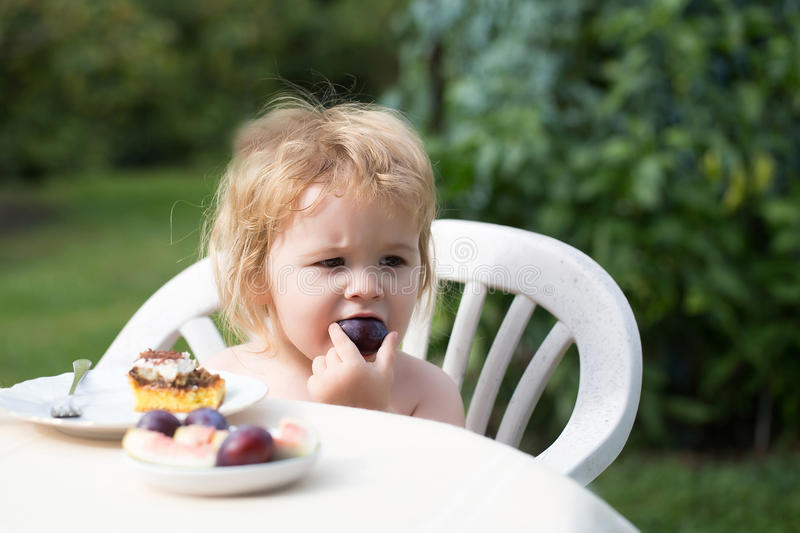 Baby boy eats plum royalty free stock images