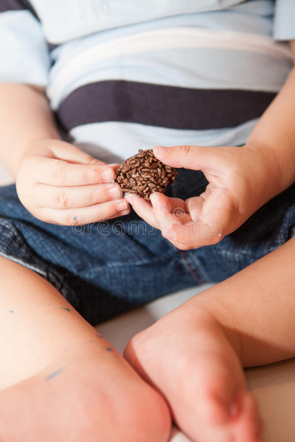 Baby boy eats small chocolate candy royalty free stock photo