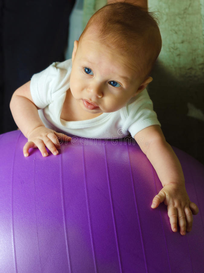 Baby boy is exercising on gymnastic ball. Concept of caring for the baby's health royalty free stock image