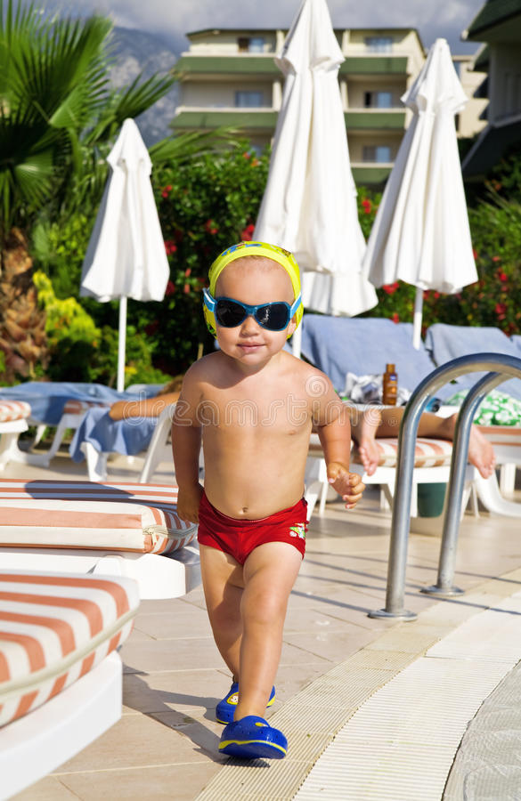 Baby boy in fashionable glasses. And in red swimming cowards running along a pool royalty free stock photography
