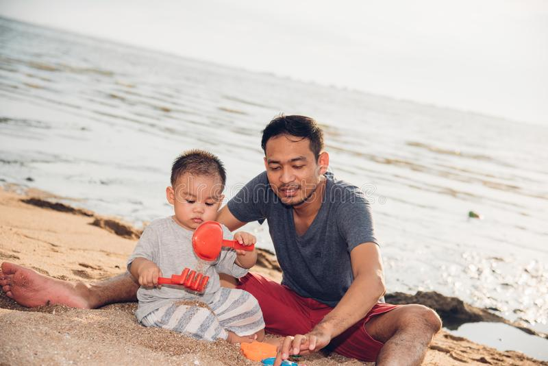 Baby boy and father dad playing fun on sand beach nature stock photography