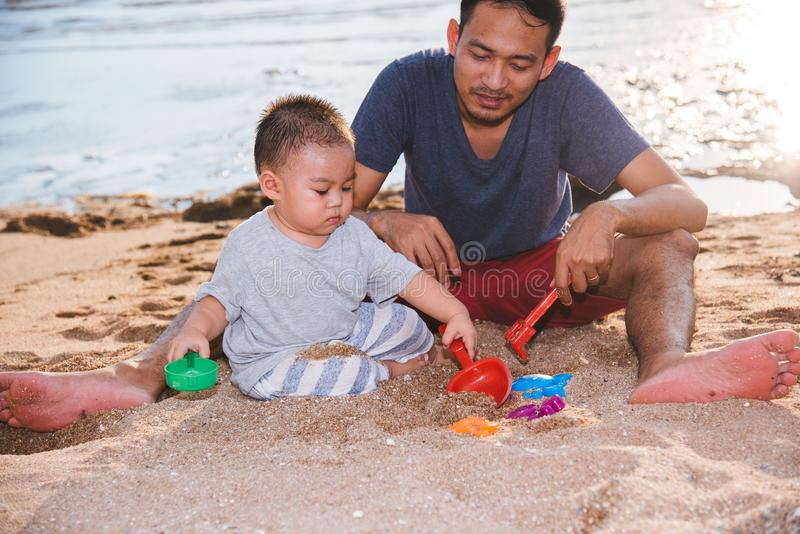 Baby boy and father dad playing fun on sand beach nature stock images