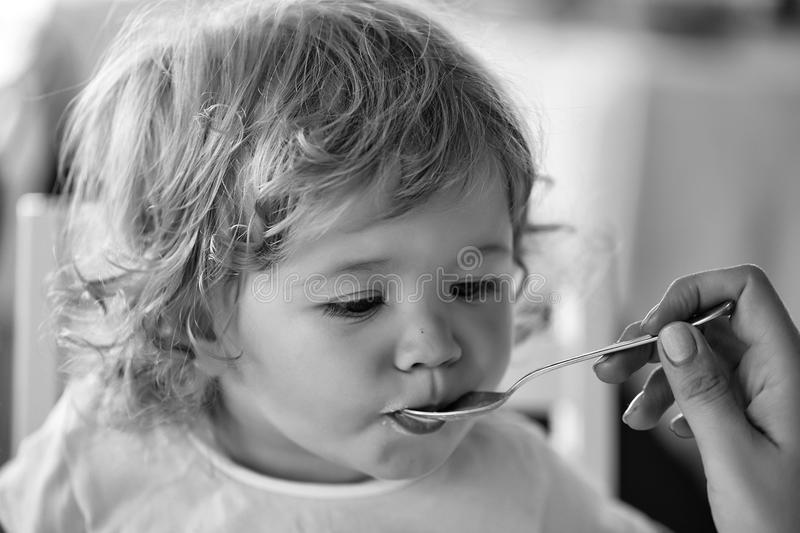 Baby boy fed with spoon. Cute fair-haired blond hazel-eyed kid little child baby boy fed with spoon eating photo portrait on blurred background, horizontal stock images