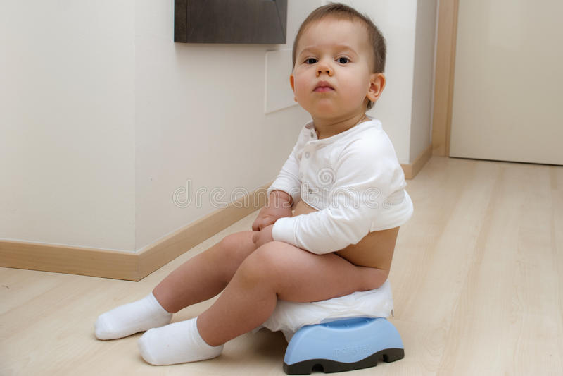 Baby boy on a folding potty royalty free stock photos