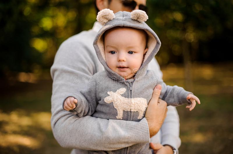 Baby boy in funny clothes on the hands of daddy outdoors stock photography