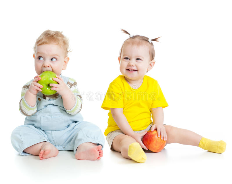 Baby boy and girl eating apples isolated. On white stock images