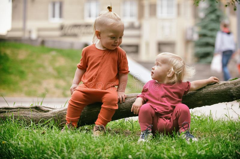 Baby boy and baby girl playing while sitting on green grass stock photography