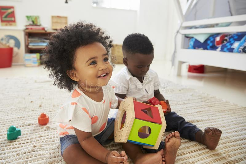 Baby Boy And Girl Playing With Toys In Playroom Together stock photo