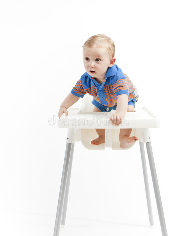 Baby boy in high chair stock photo