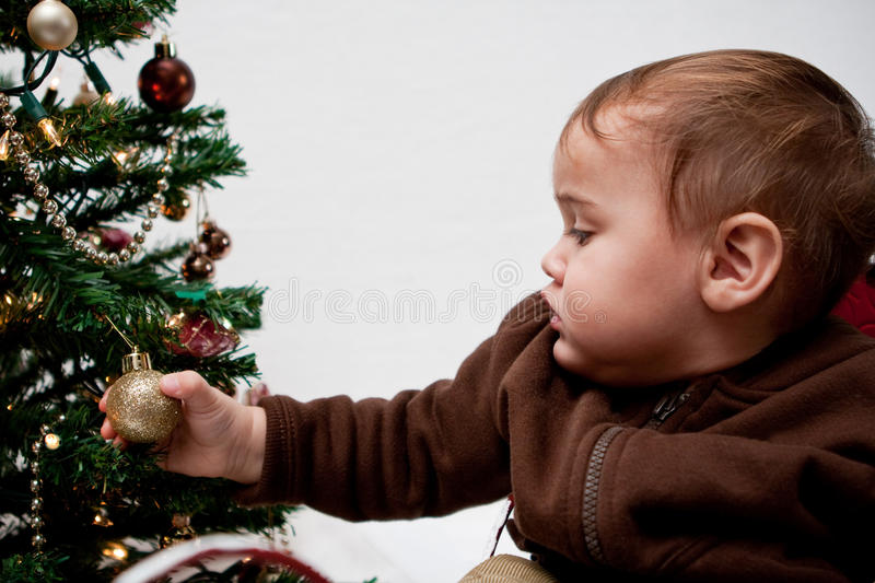 Baby boy holding Christmas ornament on tree royalty free stock photography