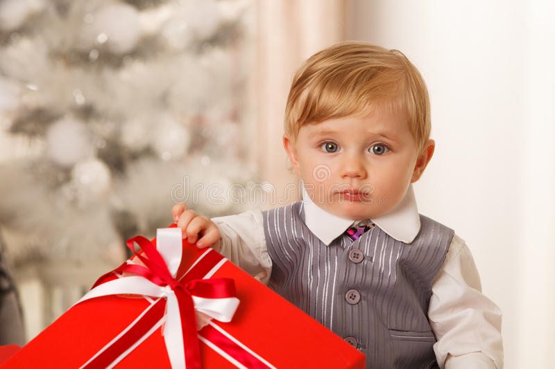 Baby boy holds a big red gift box stock images