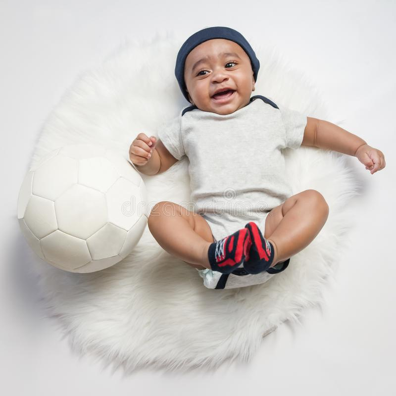 Baby boy infant fun photoshoot soccer football concept big smile having fun playing laughing laying on white furry round through s stock photography