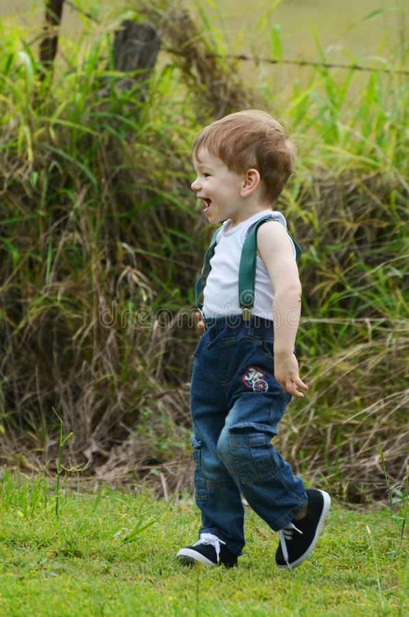 Baby boy joyful laughing & playing in country meadow royalty free stock images