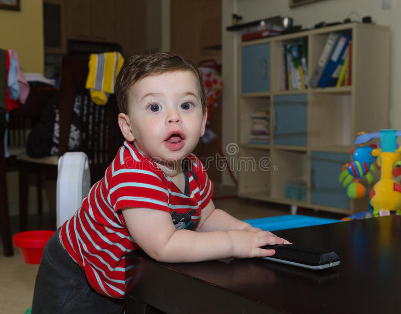Baby boy leaning on a table stock image