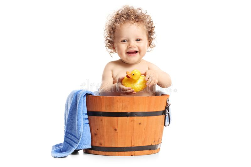 Baby boy with a little rubber duck sitting inside a wooden bucket royalty free stock images