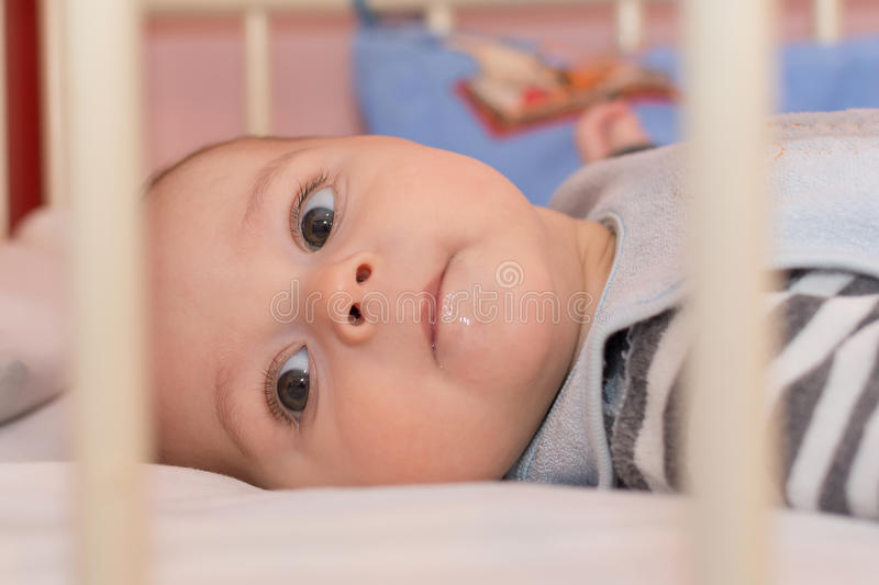 Baby boy lying on back in a white crib.  royalty free stock images