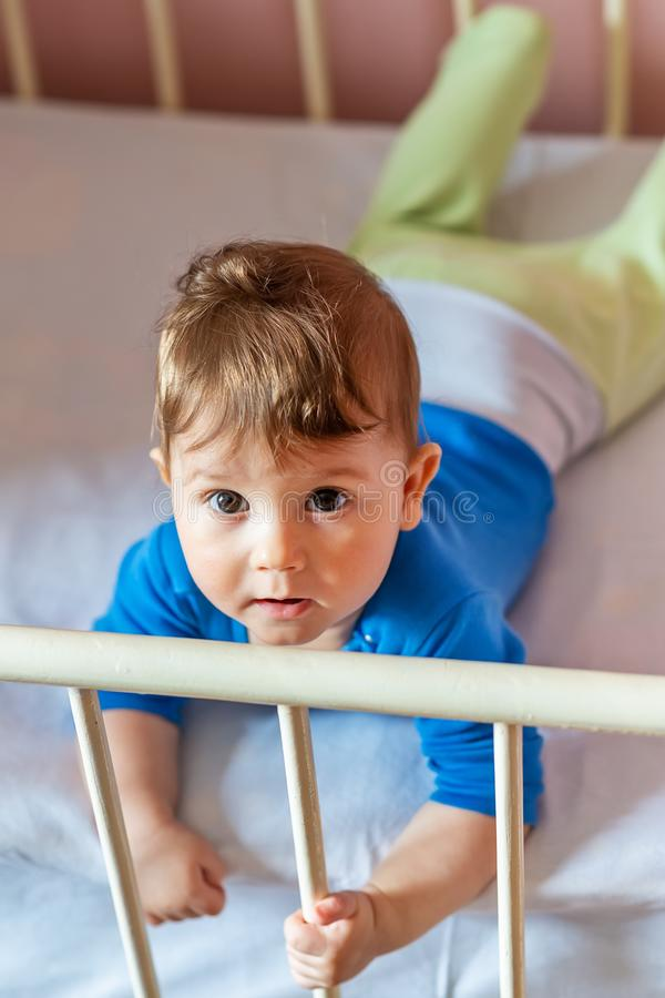 The baby boy lying on his stomach in his crib.  stock photo