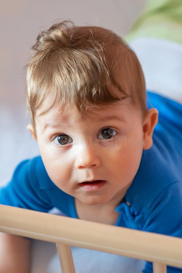 The baby boy lying on his stomach in his crib.  stock image
