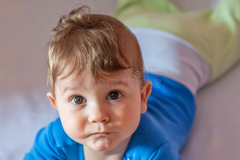 The baby boy lying on his stomach in his crib.  stock images