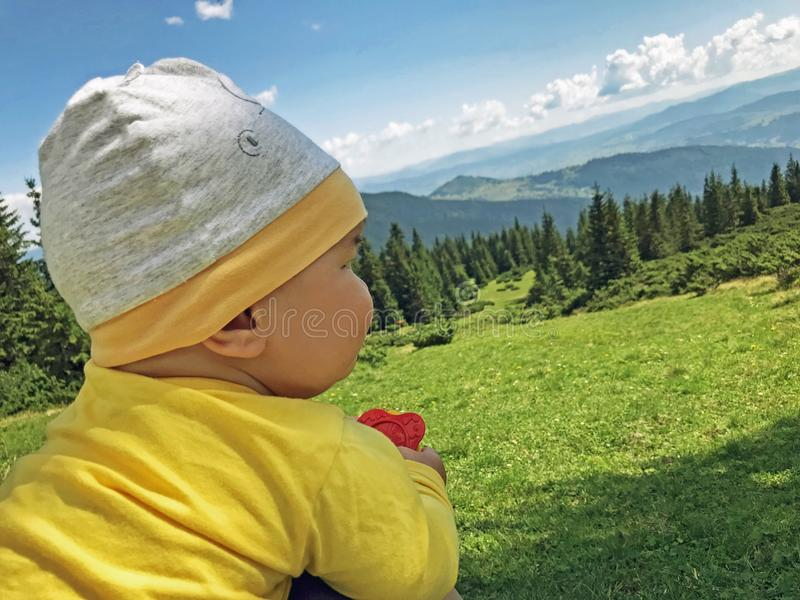 A baby boy 7 months on the grass and looking at Carpathian M stock image