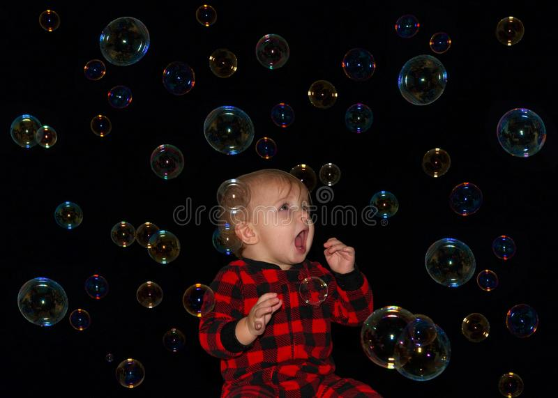 Baby boy mouth open trying to eat bubbles in air all around him stock photo