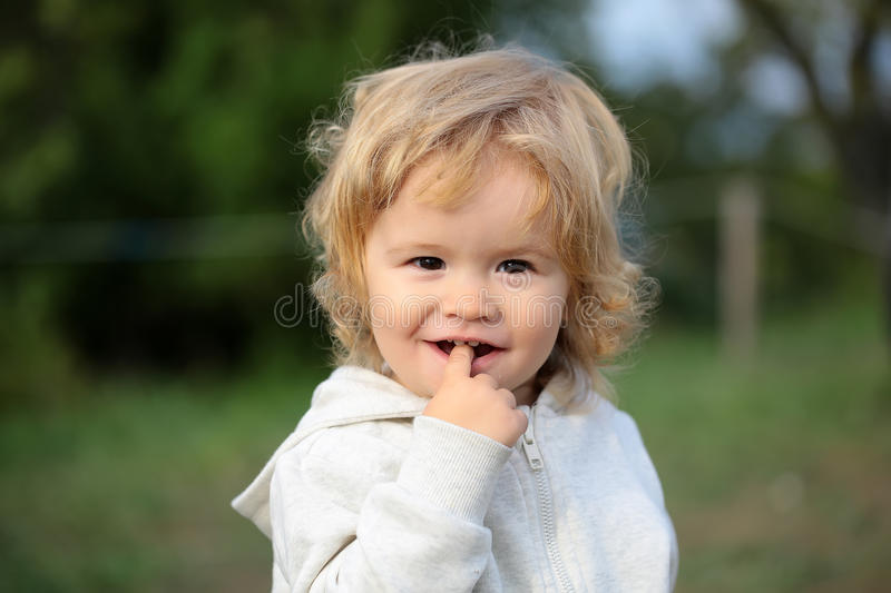 Baby boy on nature. Kid little child baby boy fair-haired blond hazel-eyed smiling wearing grey hooded coat cute portrait with finger in mouth looking at camera royalty free stock photos