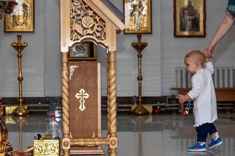 Baby boy in Orthodox church. Baby boy with mom in Orthodox church. Belarus, Starobin, June 23, 2018 stock photos