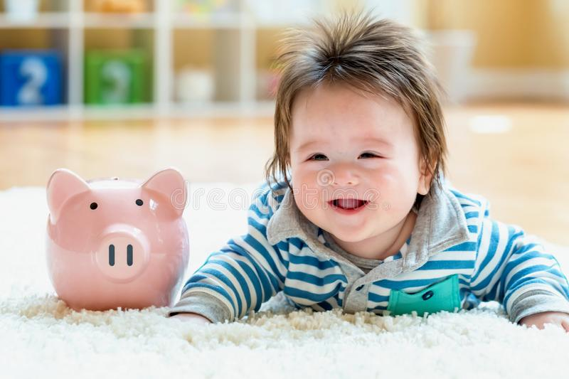 Baby boy with a piggy bank royalty free stock photography