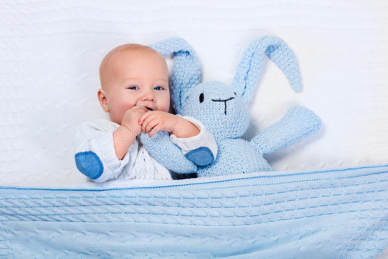 Baby boy playing with blue knitted bunny toy stock photo