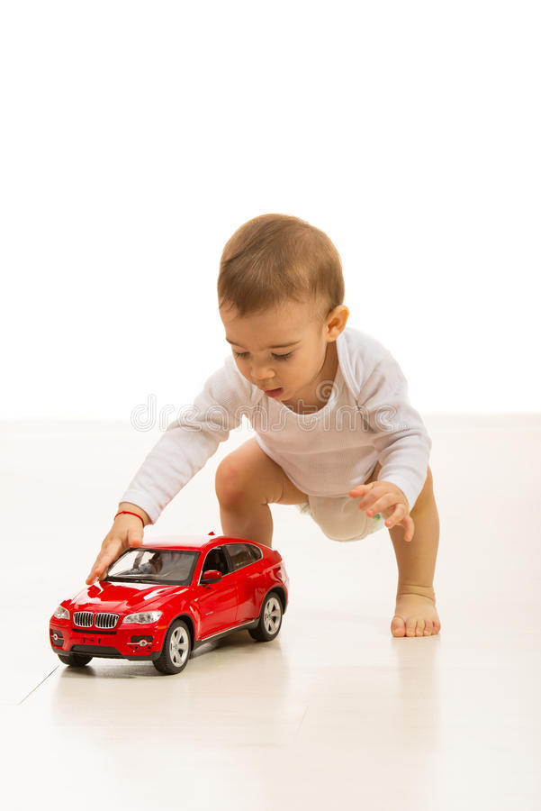 Baby boy playing with car toy. Home and standing on the floor stock images