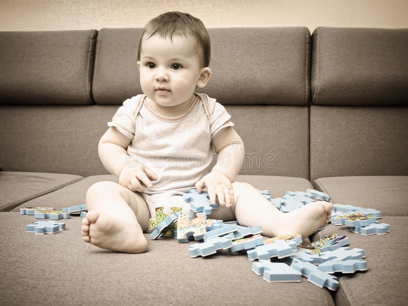 Baby boy playing with puzzle pieces on sofa in the living room at home royalty free stock photos