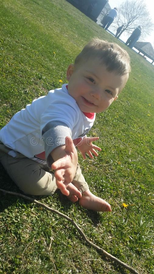 Baby boy playing in summer grass stock image