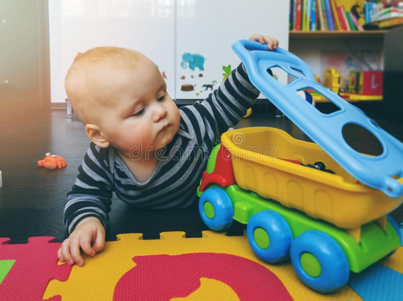 Baby boy playing with toy car on the floor at home. Nursery stock images
