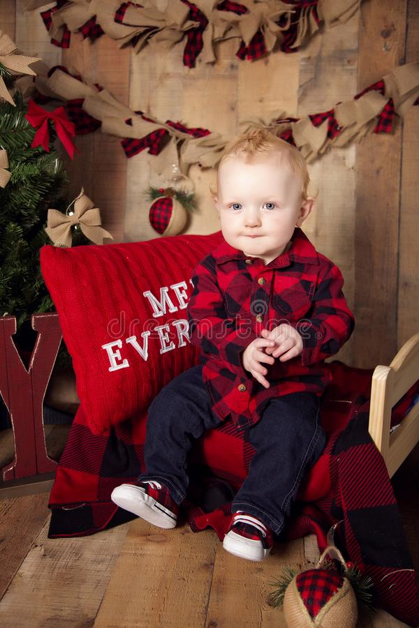 Baby boy posing on Christmas set. Blond baby boy in buffalo plaid posing on Christmas set with tree and decorations and wood planking background royalty free stock images
