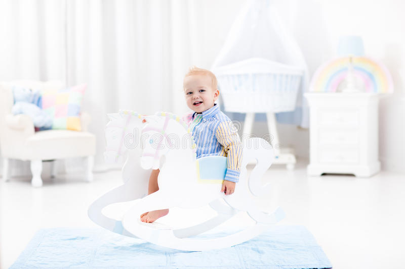 Baby boy in rocking horse toy. Cute baby boy riding wooden traditional rocking horse toy in white bedroom with pastel rainbow color decoration. Child playing in royalty free stock image