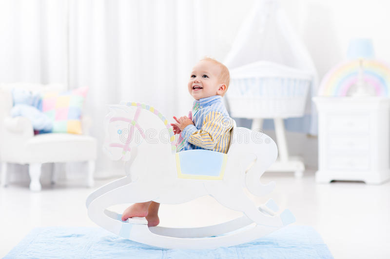 Baby boy in rocking horse toy. Cute baby boy riding wooden traditional rocking horse toy in white bedroom with pastel rainbow color decoration. Child playing in royalty free stock photo