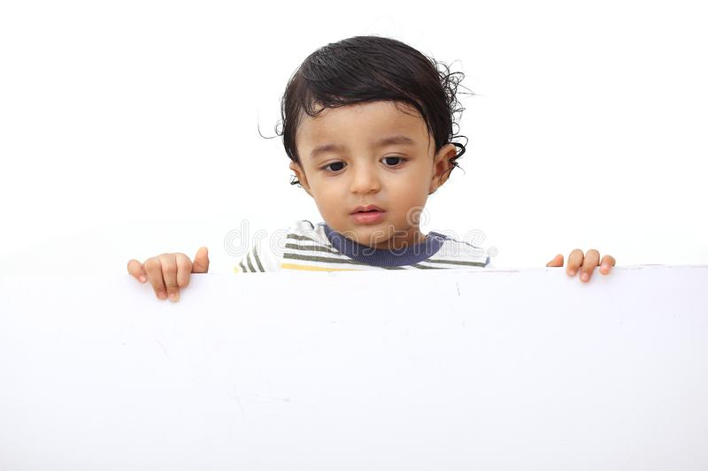 Baby boy showing copy space on blank white board royalty free stock images