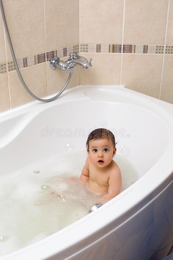Baby boy sitting in bath with water stock images