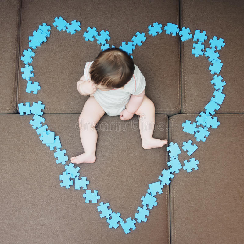 Baby boy sitting in the middle puzzle pieces folded as shape of heart on sofa at home living room stock images