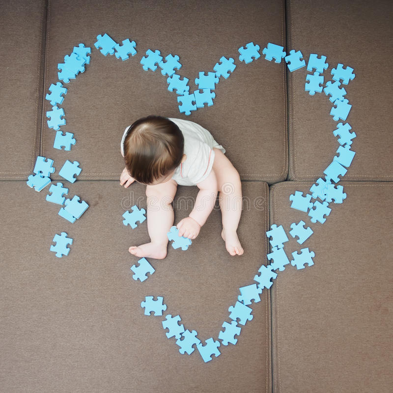 Baby boy sitting in the middle puzzle pieces folded as shape of heart on sofa at home living room stock photos