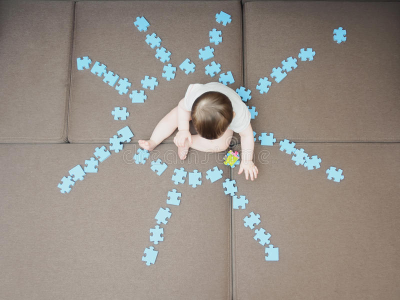 Baby boy sitting in the middle puzzle pieces folded as shape of sun on sofa at home living room stock photo