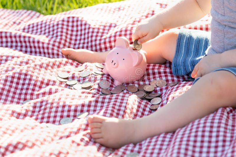 Baby Boy Sitting on Picnic Blanket Putting Coins in Piggy Bank stock image