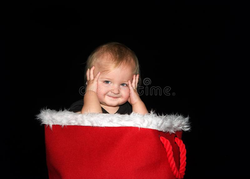 Baby boy sitting in red basket with fur lining holding sides of head smiling royalty free stock photos