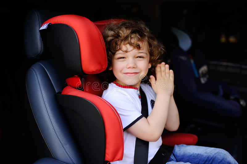 Baby boy sitting in a red child car seat. Baby boy with curly hair sitting in red child car seat in a minivan royalty free stock image